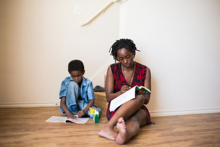 Farryn Giles colors with her son Isaiah at their apartment in Dallas.