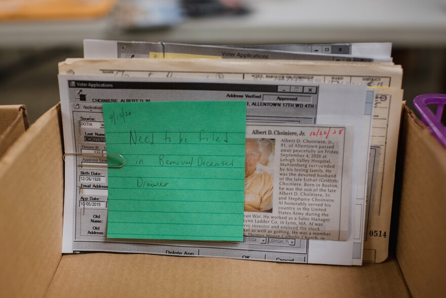 "A memo stating ""Need to be filed in Removal/Deceased Drawer"" is attached to an obituary newspaper clipping. Election workers check obituaries to make sure ballots are not sent to people who have died."