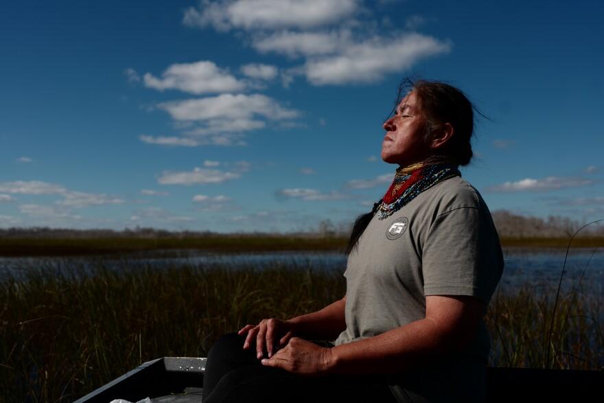 Miccosukee grandmother Betty Osceola prays on her airboat in the Everglades, Ochopee, Fla., on January 7, 2021.