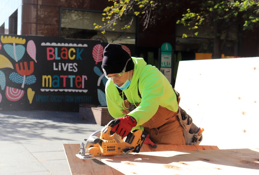 Joe Heilbrunn saws boards to cover windows in downtown Columbus.