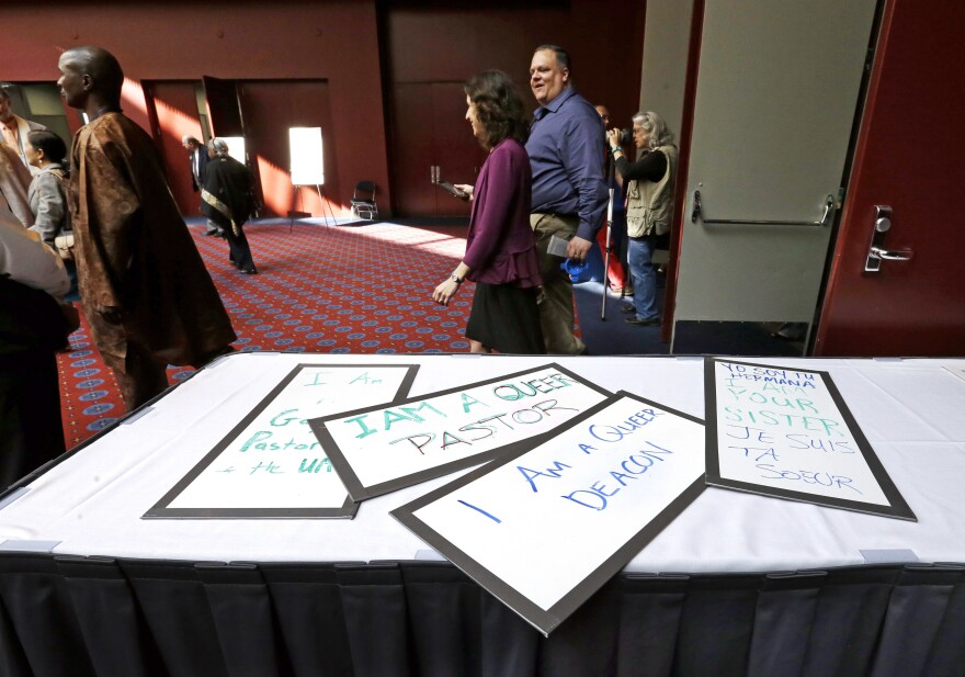 Attendees walk past a handful of placards during a break in the Methodists annual conference in Portland, Ore., in May 2016. The United Methodist Church, the nation's largest mainline Protestant denomination, was holding its once-every-four-years meeting and is facing a bitter fight over whether it should lift the church ban on same-sex marriage.
