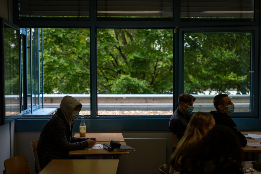 Students sit in classroom at a secondary school in Brühl, Germany, outside of Cologne, on Oct. 8, 2020, with windows wide open to provide air circulation. Ventilation is an official part of the government's strategy to prevent Coronavirus spread in schools. Older students are again required to keep masks on all day as cases in the state of North Rhine-Westphalia rise.