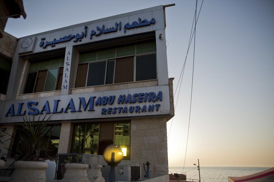 The sun sets over Al Salam Abu Haseira fish restaurant by the beach.