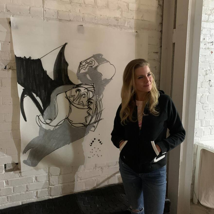 Aimee Wissman at Returning Artist Guild in front of her artwork