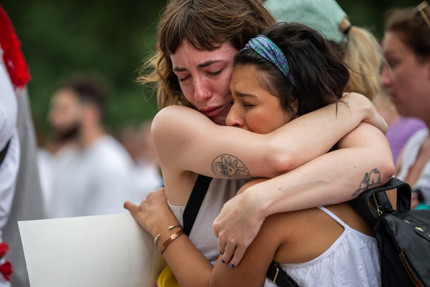 Katie Drackert (left) and Karla Arias hug