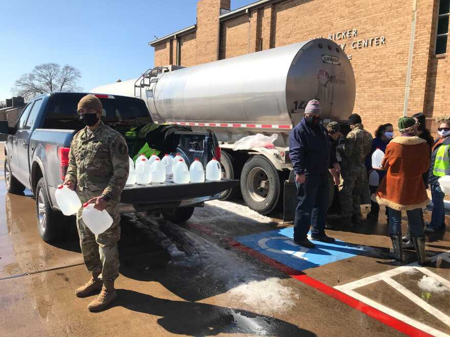 Volunteers, city workers and members of the Texas Army National Guard help distribute water to residents.