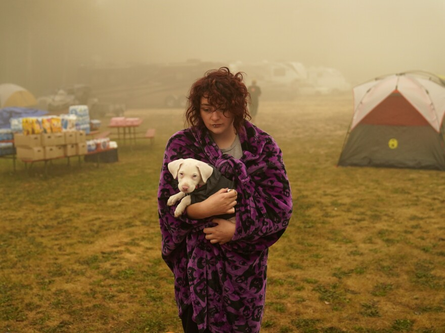 Shayanne Summers holds her dog Toph on Sunday after several days of staying in a tent at an evacuation center at the Milwaukie Portland Elks Lodge in Oak Grove, Ore.