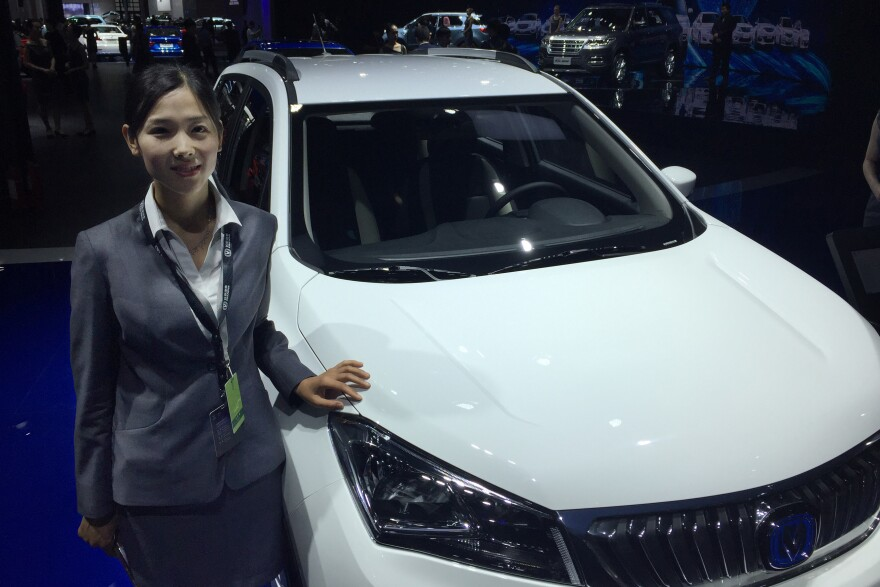 Tong Xiuying of Chinese automaker Chang'an stands in front of her automaker's first electric SUV, which will go on sale at the end of this year.