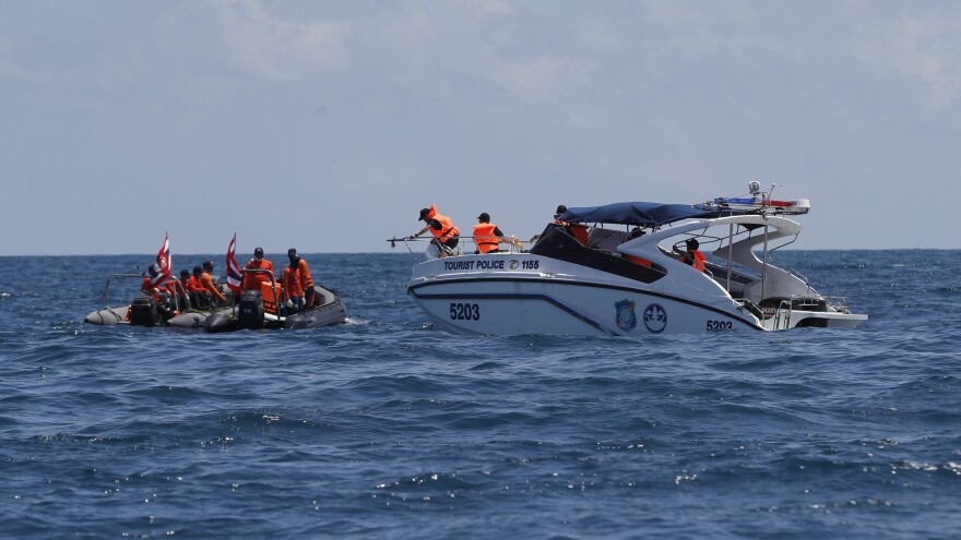Thai rescue divers and a tourist police boat conduct a search mission for missing passengers from a capsized tourist boat off Phuket, Thailand, on Saturday.