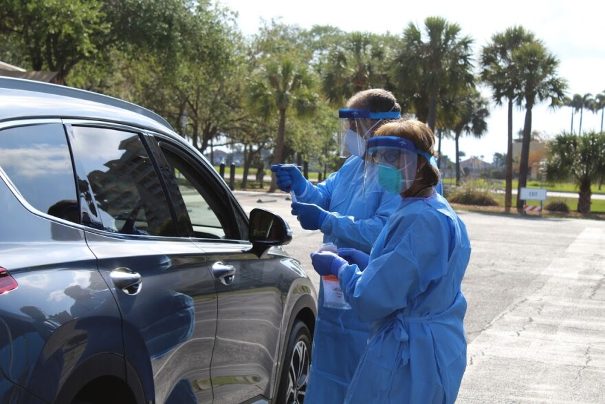 A man and woman in blue scrubs and face shields near a car at a drive-thru COVID-19 testing site.