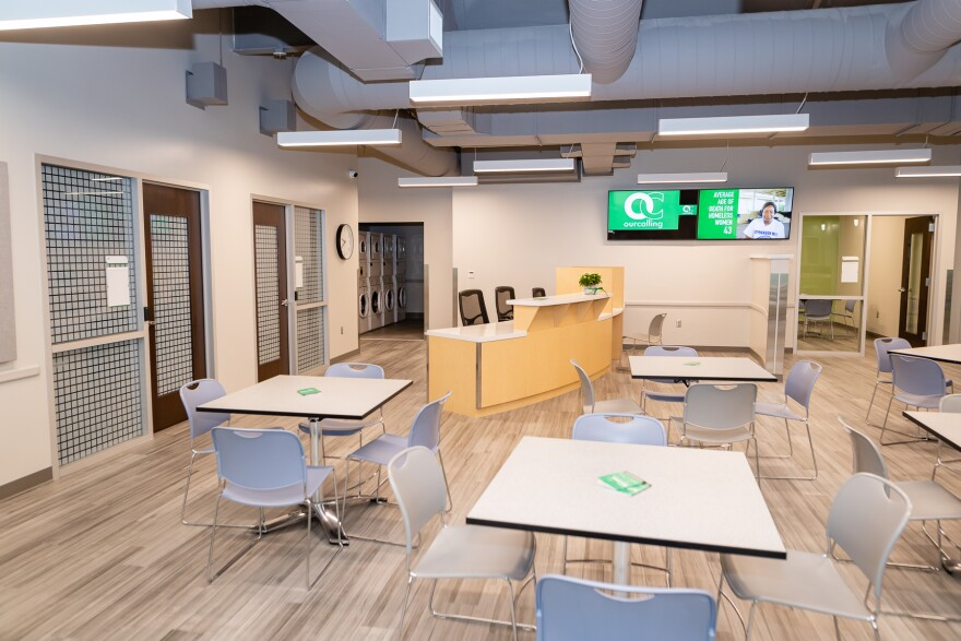Tables and chairs are laid out in the reception area of the new women-only wing. New washing machines are in the back and counseling rooms are on the left.