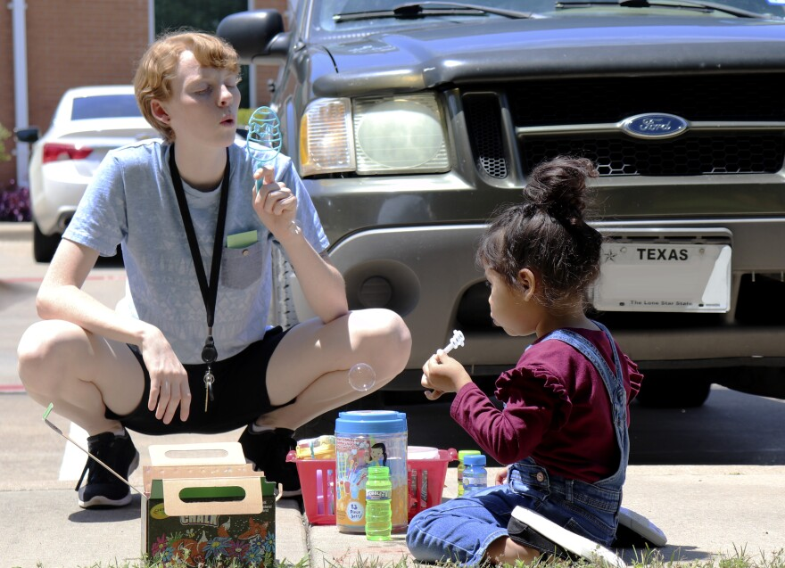 Children's caregiver at SafeHaven plays outdoors with a small child before coronavirus outbreak.