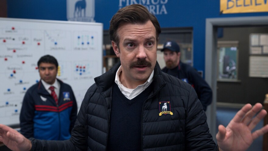 Actor Jason Sudeikis as his character Ted Lasso in center of the frame, hands outspread, addressing the soccer team he coaches.