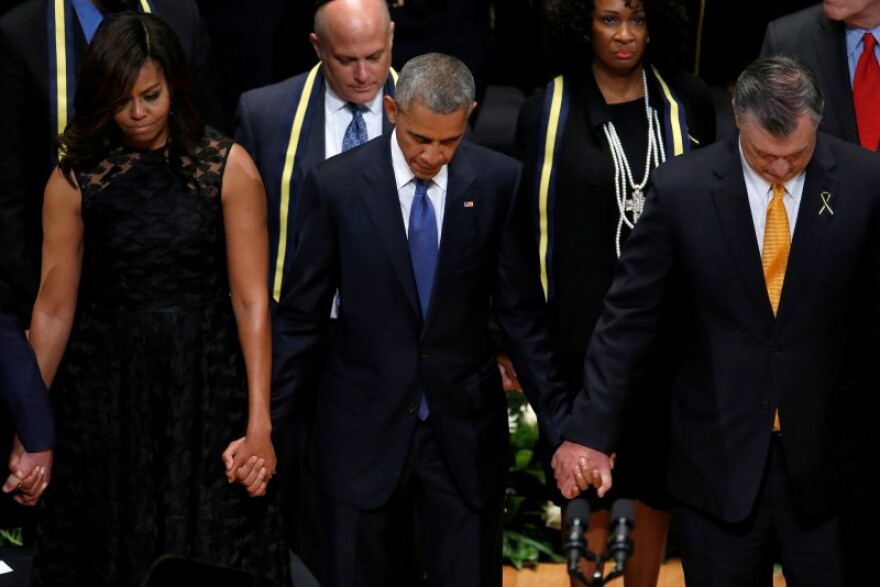 President Obama helds hands with his wife, Michelle, and Dallas Mayor Mike Rawlings at the interfaith memorial service in Dallas Tuesday afternoon.