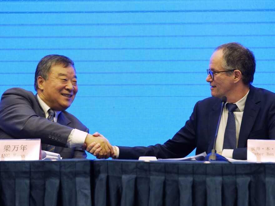 "Peter Ben Embarek, of the World Health Organization team (right) shakes hands with Liang Wannian, his Chinese counterpart, after a news conference on Tuesday in Wuhan, China. The White House says it has ""deep concerns"" over how initial findings were communicated."