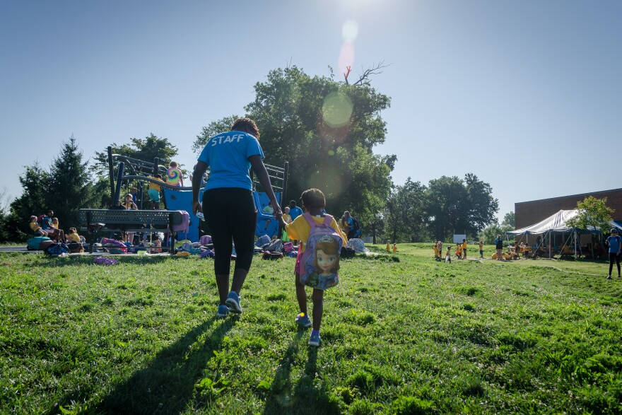 A counselor guides a camper toward the playground during a summer camp Aug. 1, 2019, at the Carondelet YMCA. Summer camps and school programs are up in the air because of the ongoing coronavirus pandemic.