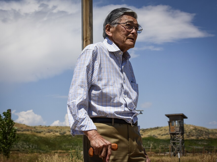 Former Commerce Secretary Norman Mineta walks past a guard tower at the site of a former prison camp near Heart Mountain, Wyo., where he and his family were wrongfully incarcerated during World War II.