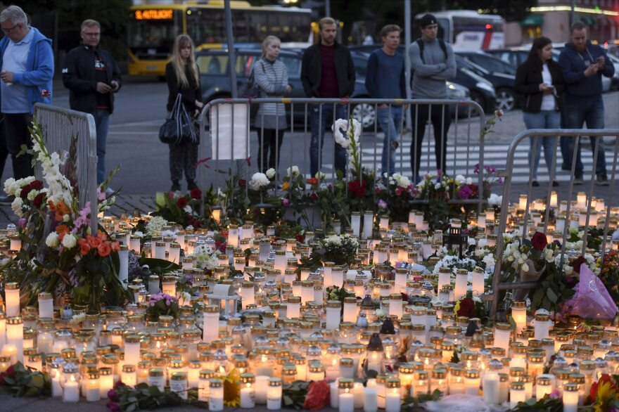 Candles and flowers left at the makeshift memorial for the victims of Friday's stabbings at the Turku Market Square, Finland.