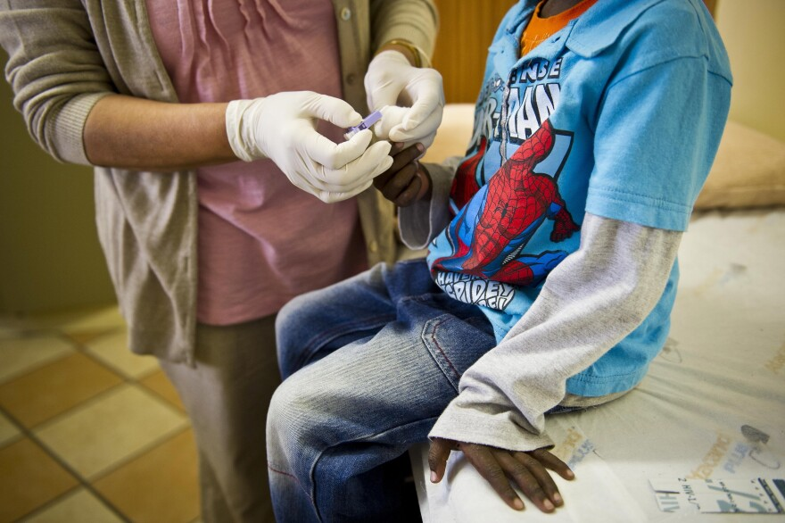A staffer at the Right to Care AIDS clinic in Johannesburg administers an HIV test on a young boy. South Africa is one of the countries that receives funds from the U.S. President's Emergency Plan for AIDS Relief (PEPFAR).