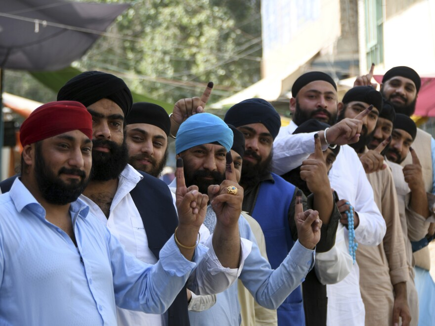 Afghan Sikhs show their inked fingers after casting their votes at a polling station in the city of Jalalabad, east of Kabul, Afghanistan, on Saturday.