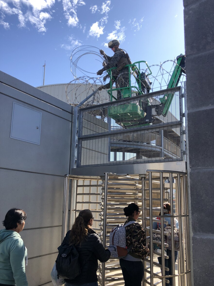 Marines install concertina wire at the San Ysidro, Calif., port-of-entry, as people enter a secure area en route to Mexico. San Ysidro is the world's busiest border crossing.