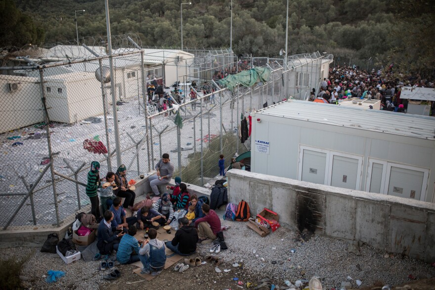 Asylum-seekers gather outside a camp on the island of Lesbos where they're supposed to be screened quickly. But sometimes the wait can last days.