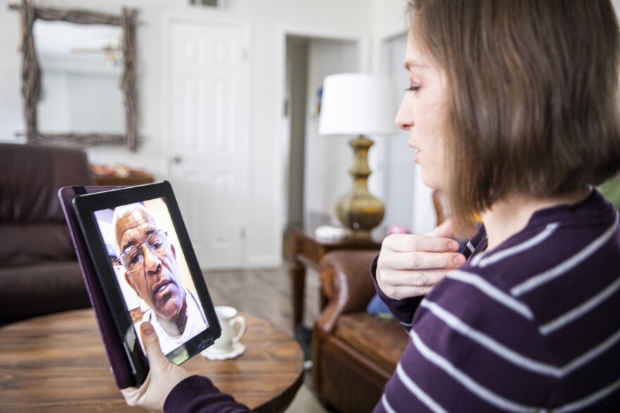 A woman talks to her healthcare provider on a tablet.