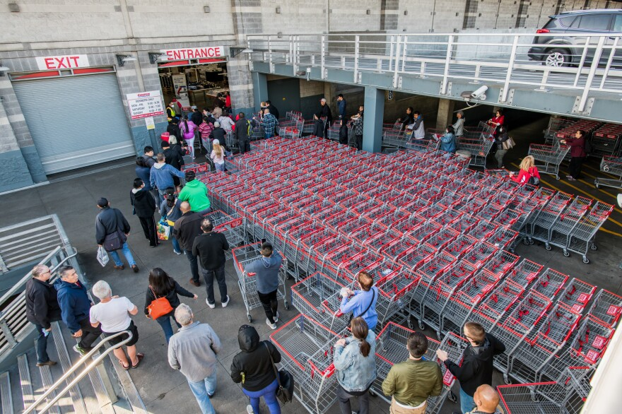 """(Top) Two children ride a scooter near San Francisco's Golden Gate Bridge, which is largely devoid of foot traffic. (Bottom) Shoppers lined up at Costco before the store opened last Friday in San Francisco. Days later, a <a href=""""https://www.kqed.org/news/11806988/sheltering-in-place-what-you-need-to-know"""">shelter-in-place</a> order took effect for much of the Bay Area."""