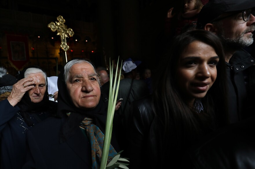 Syriac Orthodox pilgrims carry palm branches during the Palm Sunday procession at the Church of the Holy Sepulchre in Jerusalem's Old City.