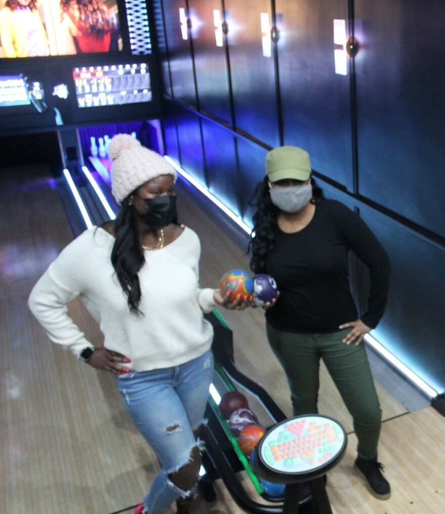 Sharise Crumley of Southfield, Mich., and Linnea Nelson of Oakpark, Mich., hold bowling balls inside Luxury Strike, a mobile bowling alley. The balls here weigh about 3-4 lbs and don't have any holes.