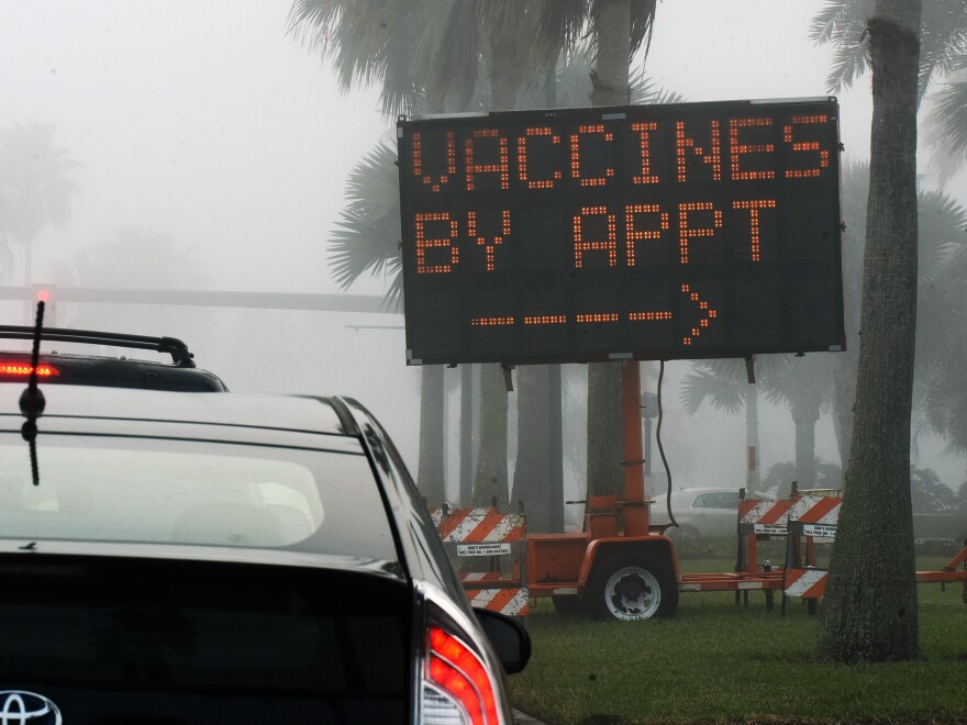 "A sign directs drivers to a COVID-19 vaccination site at the Orange County Convention Center in Orlando, Fla. Health officials in Orange County said on Thursday that two women under the age of 65 were caught dressing up as ""grannies"" in an effort to cut the vaccine line."