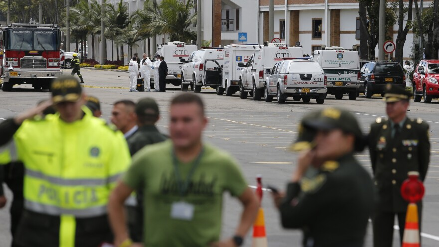Forensic workers gather at the scene of a deadly car bombing at a police academy in Bogotá, Colombia, on Thursday.
