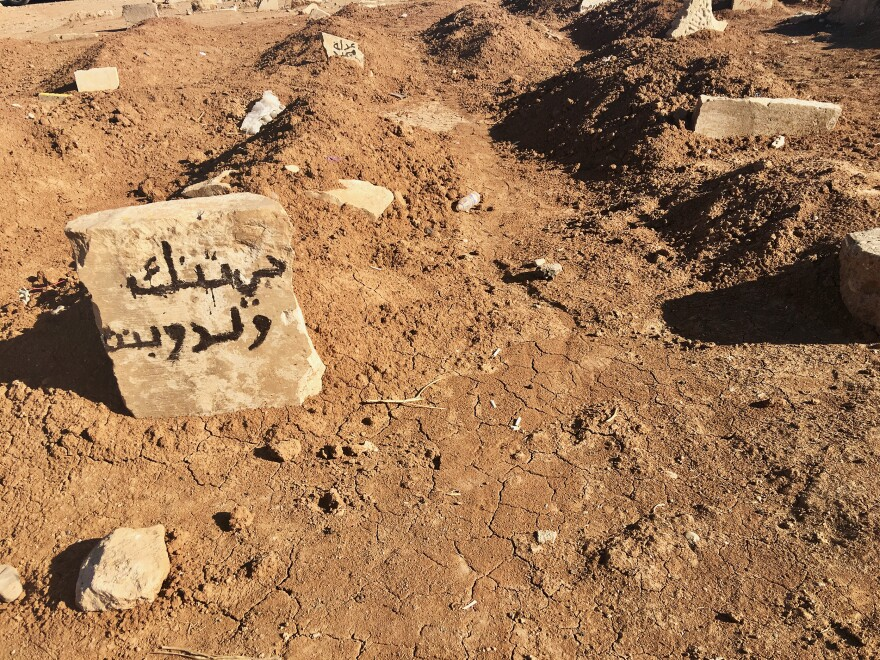 """A headstone in Mosul cemetery bears the words """"boy and girl,"""" along with the name of the neighborhood where they died. By some counts, more than 5,000 civilians died in nine months of fighting in Mosul – more than the number of ISIS fighters killed."""