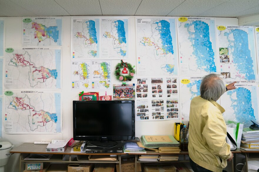 Maps hang on the wall of the lab where the Kobayashis do radiation testing. The maps, one part of their work, were created by a team of volunteers who took air measurements. The maps show that the radiation levels in Fukushima are decreasing.