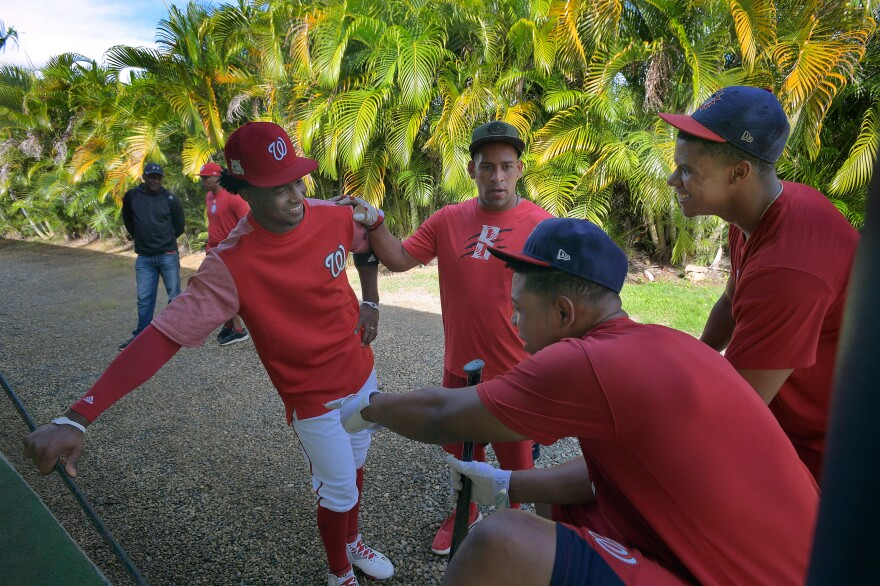 Nationals outfielder Victor Robles (left) talks with prospects Adderlng Ruiz (left to right), Luis Villorio and Soto at the team's Dominican Republic training camp in Boca Chica in January 2018. Soto was called up to the majors four months later.