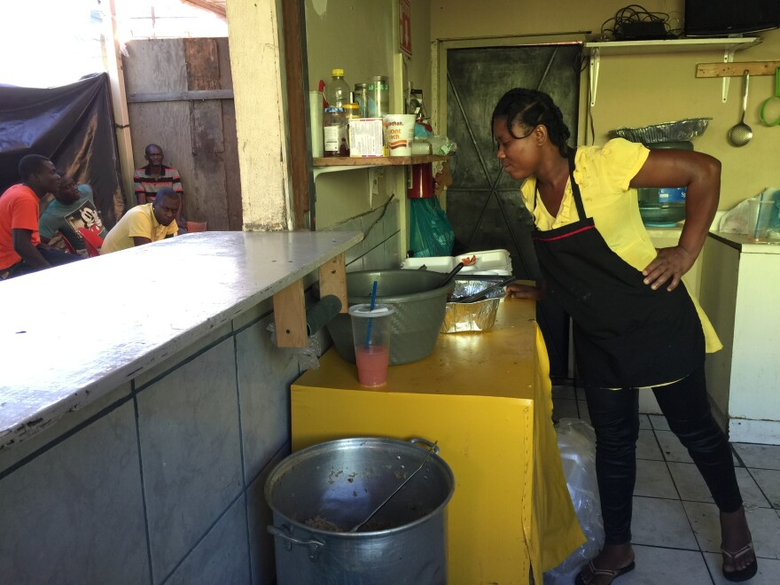 Chantale Joseph looks over a pot of Haitian rice and beans she's prepared for refugees living in Tijuana, Mexico. Recently, the eatery switched from Mexican fare to an all-Haitian menu. It's become a hangout for many Haitian refugees in the city.