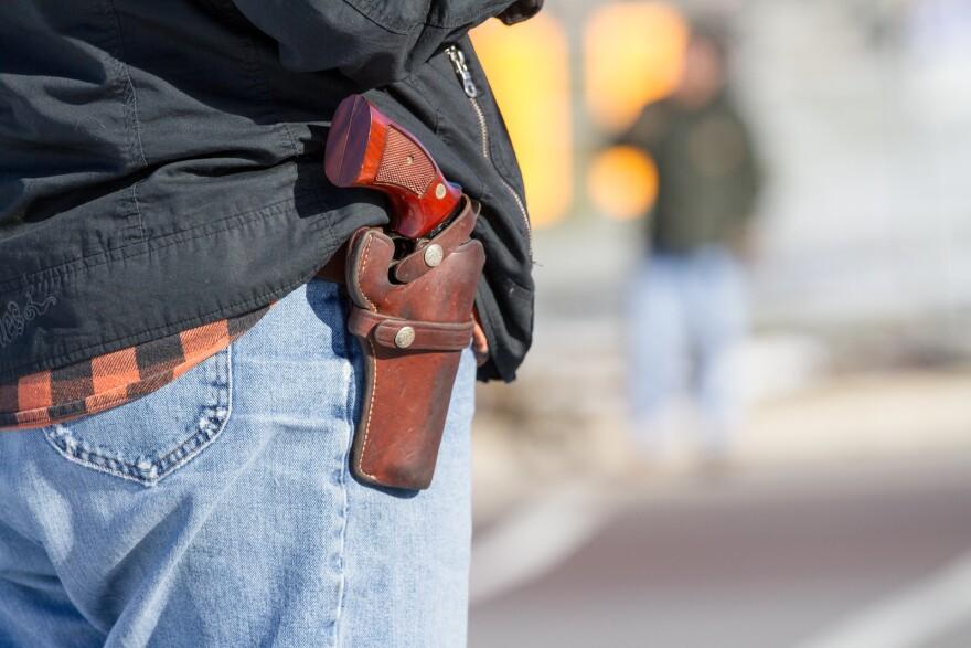 A woman wearing jeans and a handgun hip holster