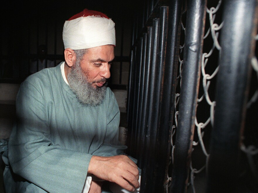 Blind Sheikh Omar Abdel Rahman sits and prays inside an iron cage at the opening of a court session in Cairo in 1989.