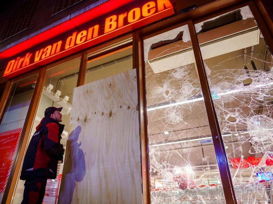 Protesters threw fireworks and rocks at police, damaged storefronts, and looted stores during demonstrations on Monday in the Netherlands.