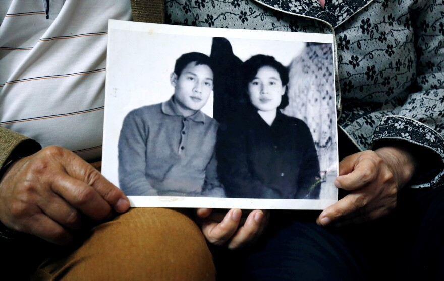 Canh and Ri hold a photo from their early days of courtship in 1971, when he was in North Korea on an internship.