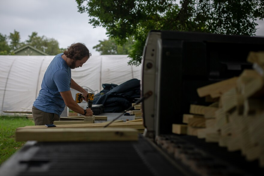 Gateway Greening's Jackson Hambrick works on building benches for schools to use in outdoor classrooms. Public health experts say schooling should be conducted outside as much as possible to limit virus spread.