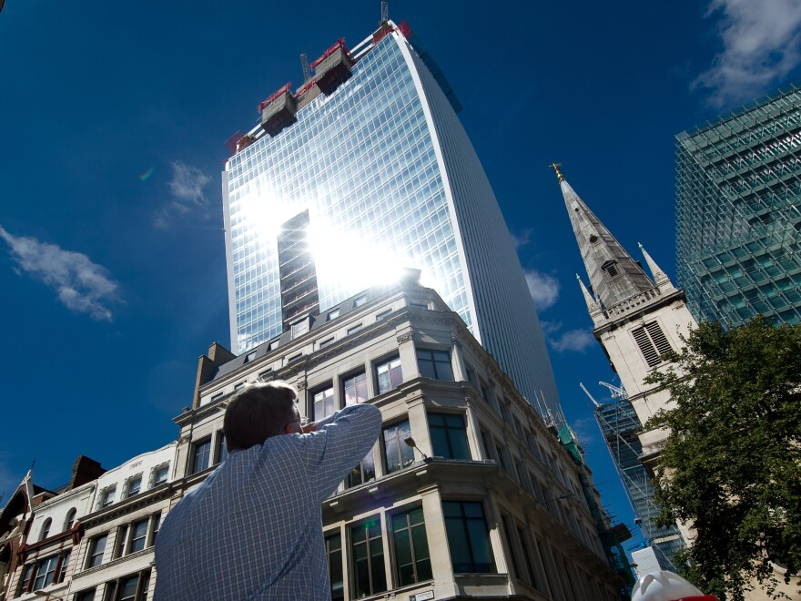 """A man reacts to a shaft of intense sunlight reflected from the glass windows of the new """"Walkie Talkie,"""" or """"Walkie Scorchie,"""" tower in central London on Aug. 30, 2013."""
