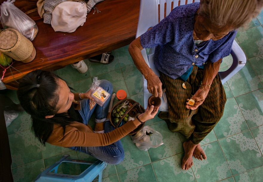 A passes <em>paan — </em>a stimulant chew made of betel leaves and other ingredients — to her grandmother. Since moving back to her home village, A spends most of her time taking care of her.