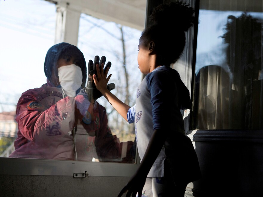 Countries under coronavirus lockdowns should only ease those restrictions if they can control new infections and trace contacts, the World Health Organization says. Here, Hashim, a health care worker, recently greeted his daughter through a glass door as they maintained social distance due to the COVID-19 outbreak in New Rochelle, N.Y.