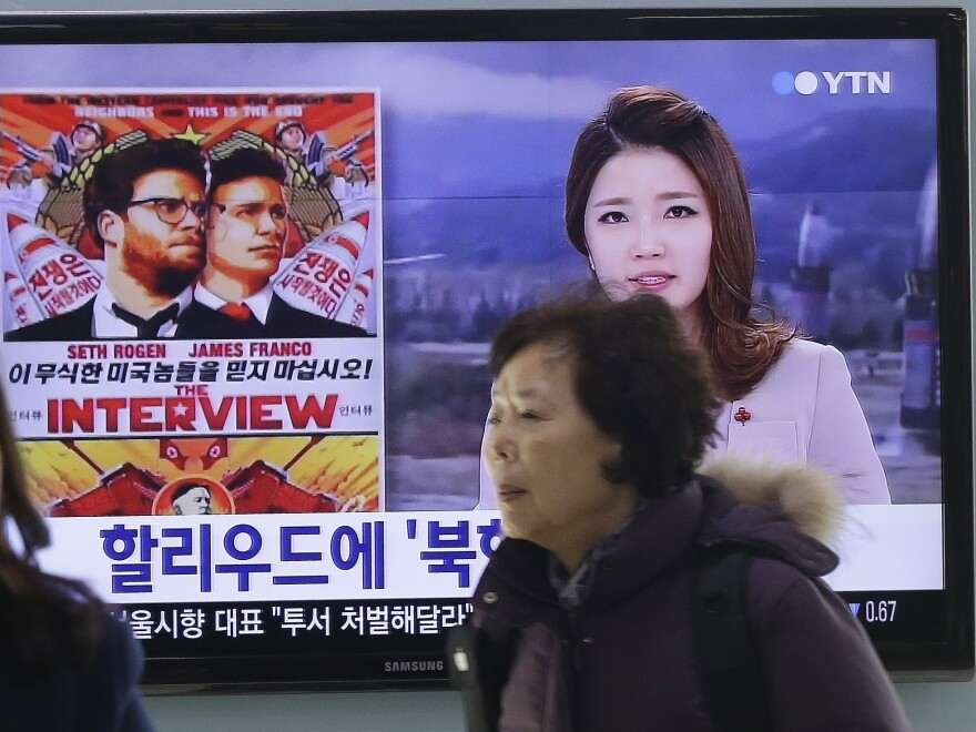 "People walk past a TV screen showing a poster of Sony Picture's ""The Interview"" in a news report, at the Seoul Railway Station in Seoul, South Korea. The FBI says North Korea hacked into Sony Pictures computer systems as retribution for the film."