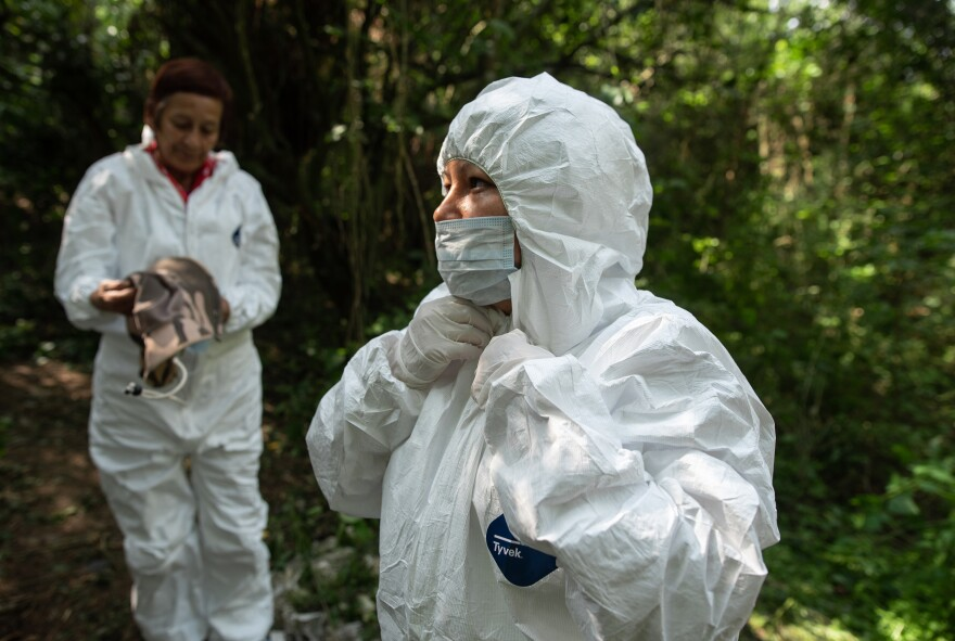 Yoltzi Martinez, 38, (right), from Guerrero, Mexico, dons a protective uniform to enter the area where a group of family members and forensic experts are searching for human remains.