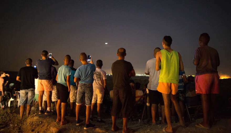 Israeli residents take photos on a hill overlooking the fighting in the Gaza Strip on July 12.