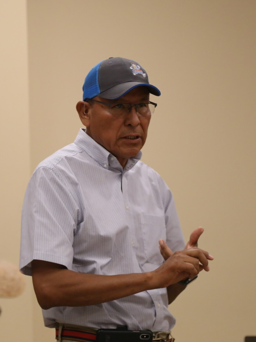 Photo of Mark Maryboya Navajo man in a button down and baseball cap stands in a room