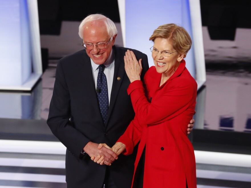 Sen. Bernie Sanders, I-Vt., and Sen. Elizabeth Warren, D-Mass., are proposing to forgive student debt for most Americans. They greet each other at a Democratic primary debate in July.