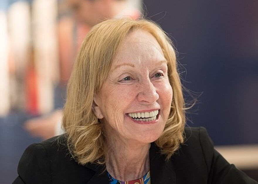 A white woman in a dark blazer with shoulder-length strawberry blonde hair smiling broadly.